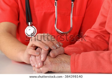 Photo of a caregiver hand touching elderly patients hand - stock photo
