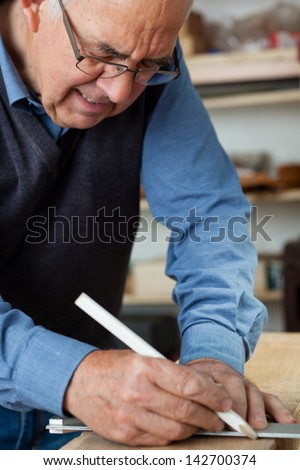 Photo of a carpenter using pencil to mark the wood in the workshop. - stock photo