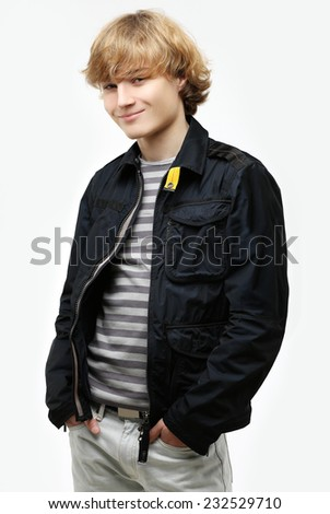 Photo of a casual blond teen standing confidently with hands in pockets. - stock photo