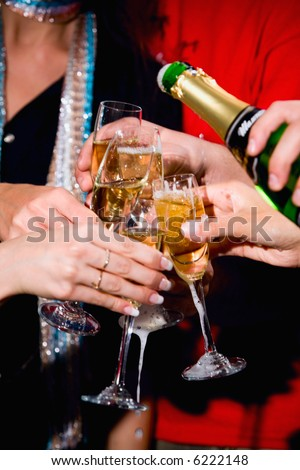 Photo of a champagne pouring into the glasses - stock photo