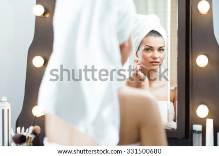 Photo of a charming woman examining herself in the mirror - stock photo