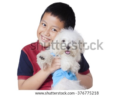 Photo of a cheerful little boy smiling at the camera while embracing a maltese dog in the studio, isolated on white - stock photo