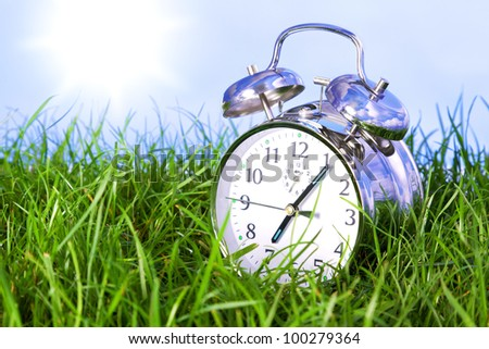 Photo of a chrome alarm clock outdoors sitting in grass on the morning of a bright sunny day. - stock photo