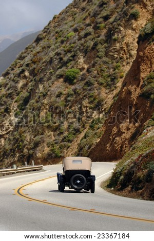 photo of a classic car taking a scenic drive along empty curvy roads