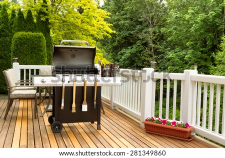 Photo of a clean barbecue cooker with cookware and cold beer in bucket on cedar wood patio. Table and colorful trees in background.