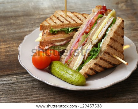 Photo of a club sandwich made with turkey, bacon, ham, tomato, cheese, lettuce, and garnished with a pickle and two cherry tomatoes. - stock photo