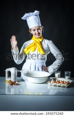 Photo of a cook waving to someone in kitchen - stock photo