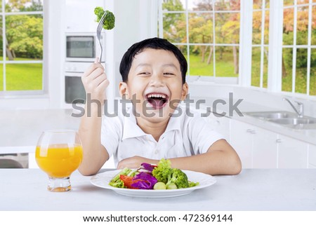 Photo of a cute little boy eating vegetables salad in the kitchen while drinking orange juice