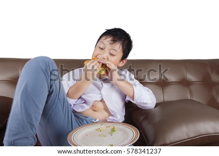 Photo of a cute little boy sitting on the couch while eating a cheeseburger, isolated on white background