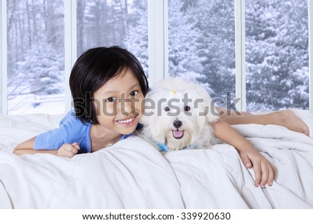 Photo of a cute little girl lying on bedroom while hugging her puppy and smiling at the camera with winter background on the window - stock photo