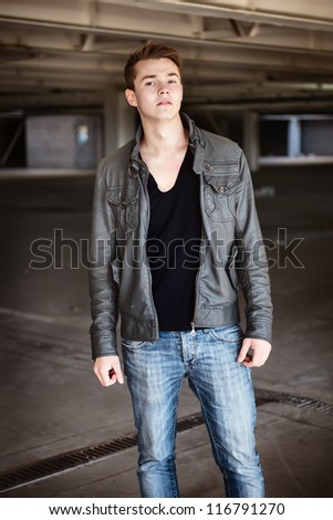 photo of a fashionable man walking in coat and jeans wear - stock photo