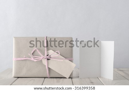 Photo of a gift box wrapped in brown paper with blank label, tied to a bow with with pale icy pink raffia.  A blank open greeting card sits beside on an old planked wooden table. Retro pastel hues. - stock photo