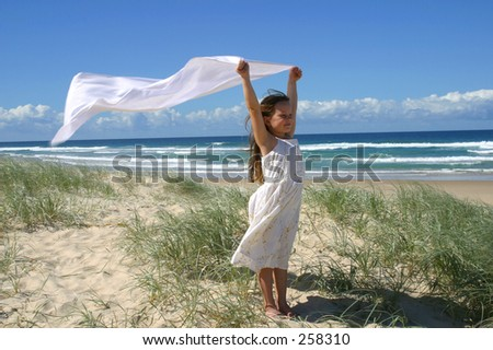 Photo of a girl on the beach with a long white cloth behind her.