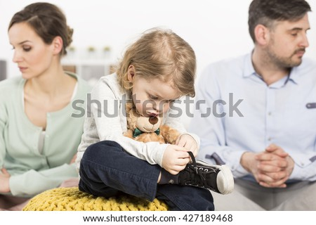Photo of a gloomy young family with a sad little boy hugging a teddy bear, and his parents with depressed looks