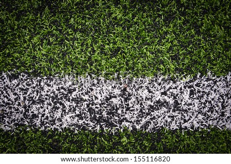 Photo of a green synthetic grass sports field with white line shot from above - stock photo