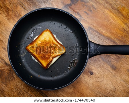 Photo of a grilled cheese sandwich cooking in a large frying pan. - stock photo