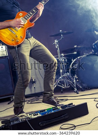 Photo of a guitar player playing on stage. - stock photo
