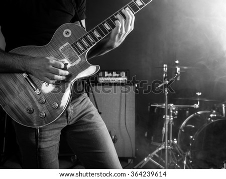 Photo of a guitar player playing on stage done in black and white. - stock photo