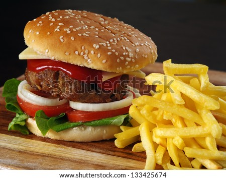 Photo of a hamburger and french fries on a wooden board.