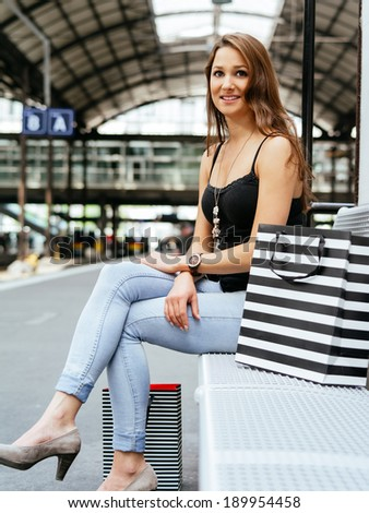Photo of a happy young woman waiting at a train station after shopping in the city.