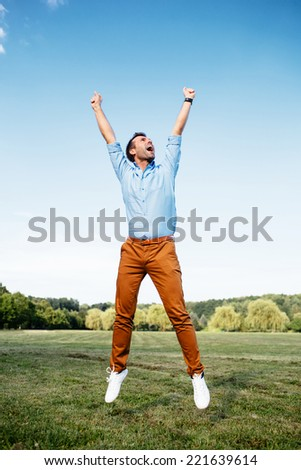 Photo of a joyful man jumping victoriously - stock photo