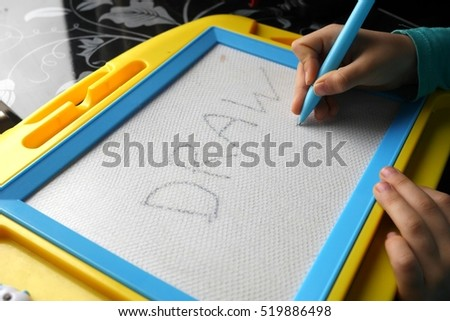 photo of a kid drawing on a magnetic drawing board education process concept learning - Kid Drawing Picture