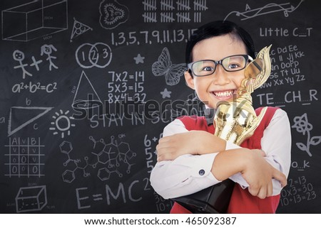 Photo of a little boy standing in the classroom while holding a trophy and smiling happy