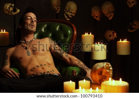 Photo of a male vampire resting in a leather chair and fangs showing.  Harsh and dark lighting for scarier feel. - stock photo