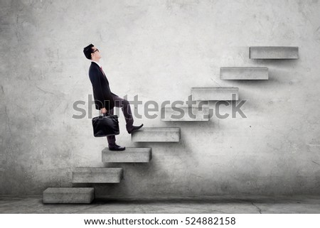 Photo of a male worker climbing upward a staircase while carrying a briefcase and wearing formal suit