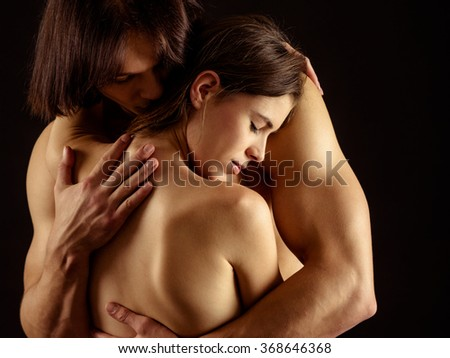 Photo of a man and woman in love and holding each other over a dark background. - stock photo