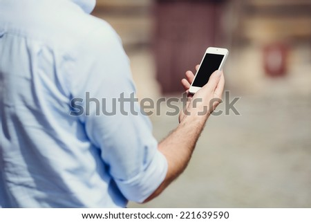 Photo of a man holding a smartphone and reading a message - stock photo