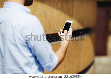 Photo of a man holding a smartphone with blank screen - stock photo