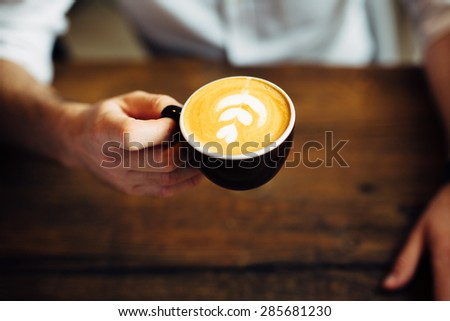 Photo of a man holding coffee cup with flower shape on foam - stock photo