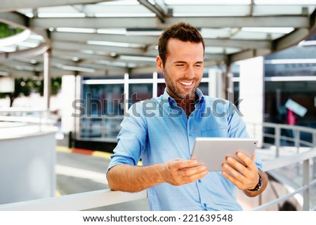 Photo of a man in the city standing and looking at his tablet - stock photo