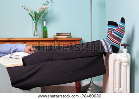 Photo of a man relaxing with his feet up on a radiator with a book on his lap and beer on the table.