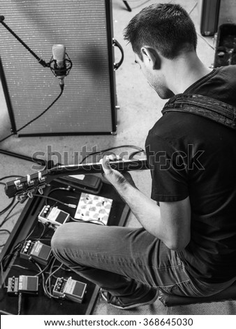 Photo of a man sitting in a recording studio recording his guitar tracks. - stock photo