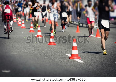 Photo of a marathon competition during an ironman. Focus on the foreground , no faces recognizable. Shallow depht of field. Use of cross processing technique to improve the drama. - stock photo