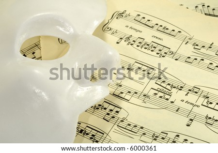Photo of a Mask on Sheetmusic - Opera / Theater Concept - stock photo