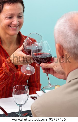 Photo of a mature couple in a restaurant toasting their glasses of red wine, - stock photo