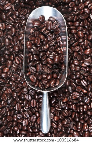Photo of a metal scoop with roasted arabica and robusta coffee beans mix.