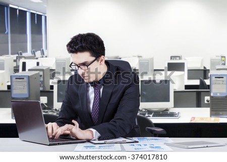 Photo of a middle eastern young businessman working with laptop computer and financial statistics in the office room - stock photo