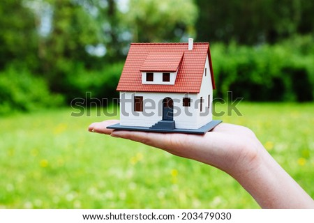 Photo of a miniature house against a green backdrop - stock photo
