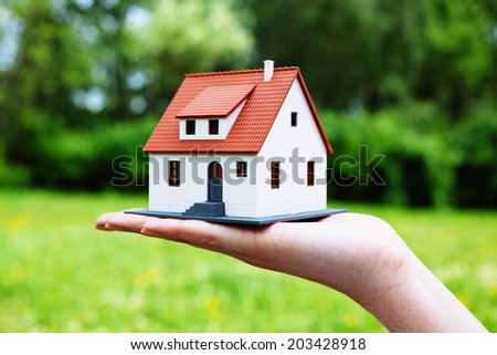 Photo of a miniature house held by a person - stock photo