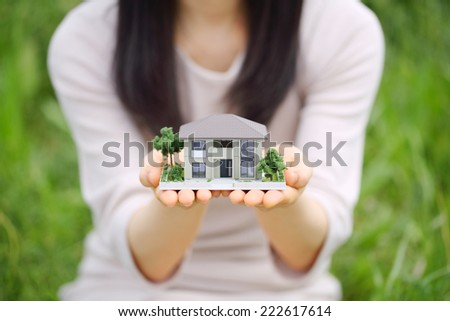 Photo of a miniature house held by a woman - stock photo