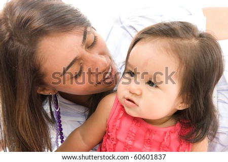 photo of a Mother kissing her daughter . - stock photo