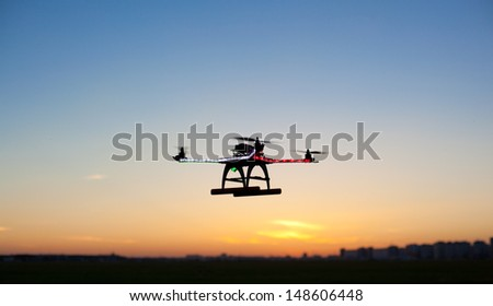 Photo of a quadrocopter on sunset sky - stock photo