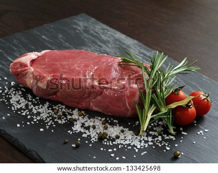 Photo of a raw thick sirloin steak with rosemary, cherry tomatoes, salt and peppercorns on a piece of black slate. - stock photo