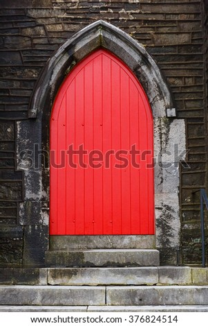 Photo of a red gothic arched church door - stock photo