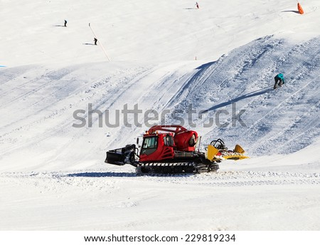 Photo of a red snowcat grooming the ski slope - stock photo