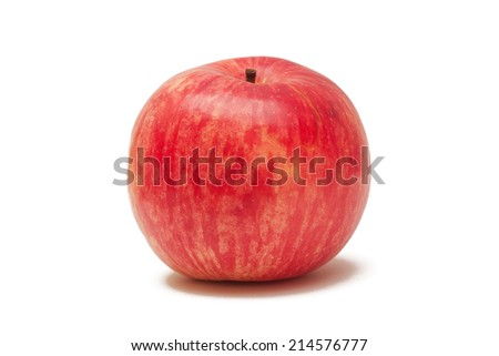 Photo of a ripe real red apple on a light yellow background